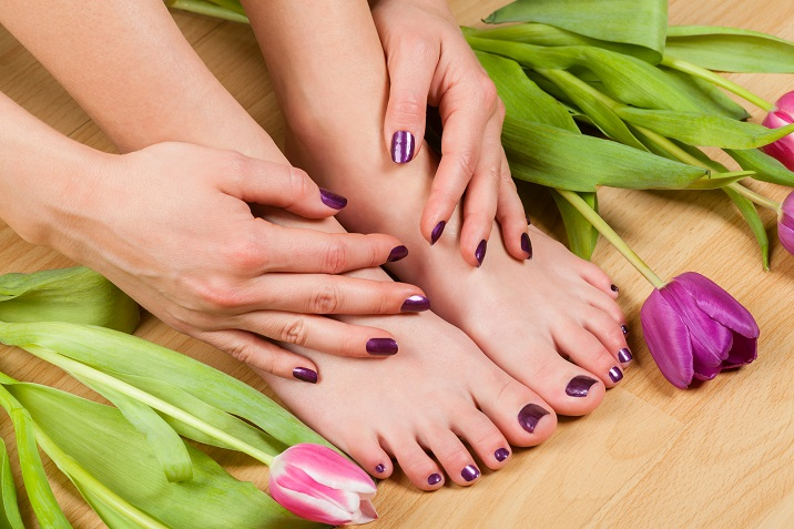 Close up of professionally done pedicure and manicure colored purple by tulips on wood floor