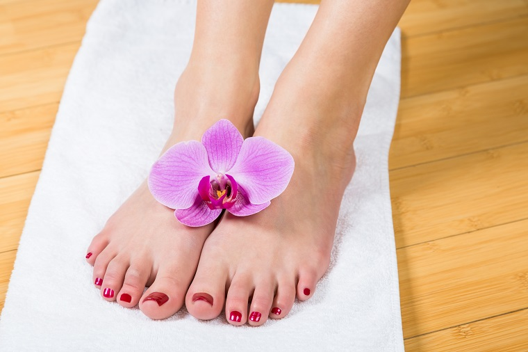 Close up on neatly painted toenails on female feet with purple flower between them over white towel