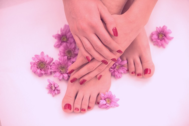 female feet and hands at spa salon on pedicure and manicure procedure