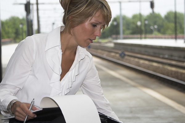 Businesswoman sitting at the trainstation checking her feet that have been in high heels all day